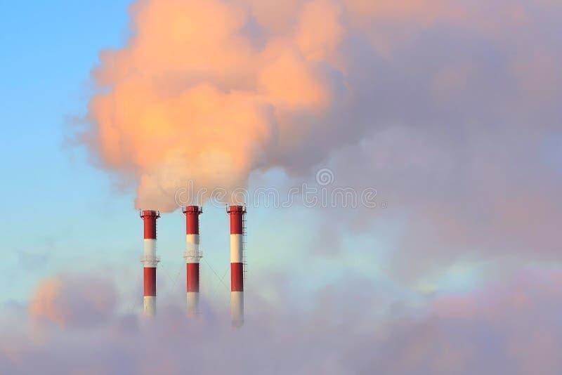 Chimenea grande tres contra el cielo y el humo imagenes de archivo