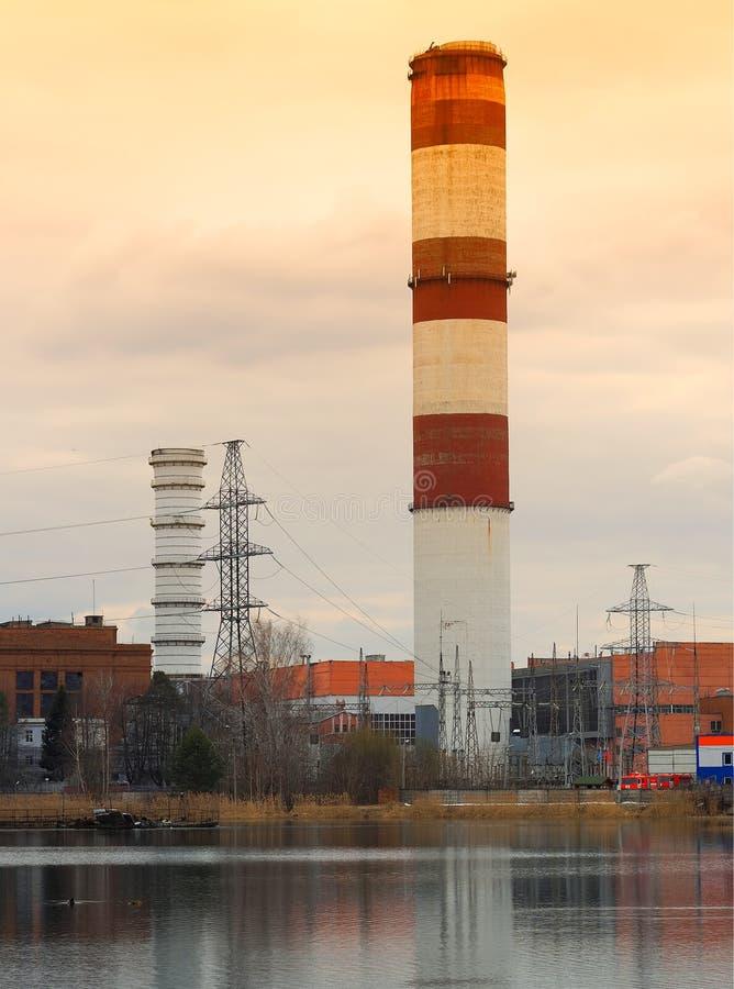 Chimenea industrial en fondo del río de la puesta del sol fotografía de archivo