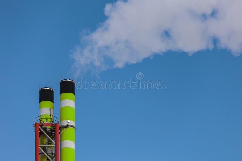 Chimenea verde de la fábrica con humo fotografía de archivo