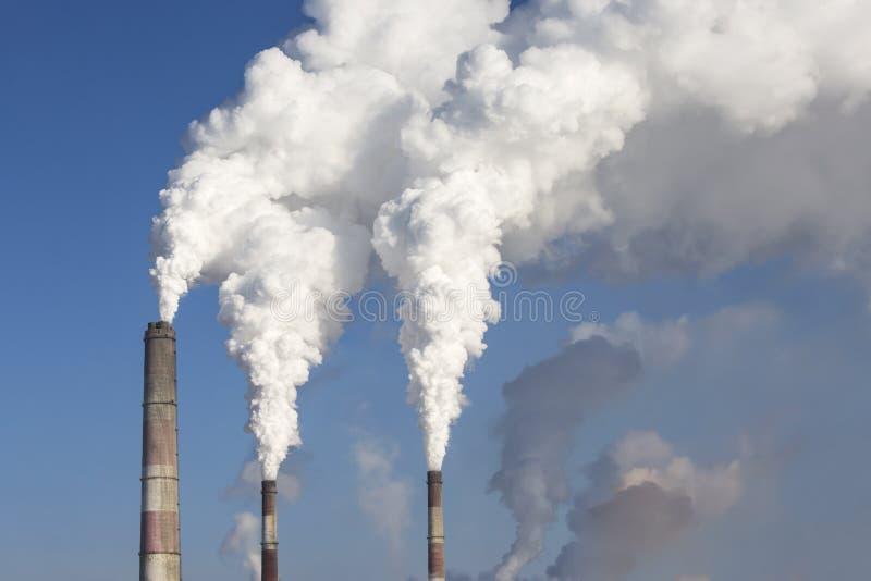 Chimeneas industriales que fuman Calor y poder combinados foto de archivo