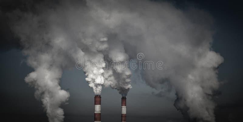 Chimeneas industriales que fuman en nubes oscuras Concepto para la protección del medio ambiente imágenes de archivo libres de regalías