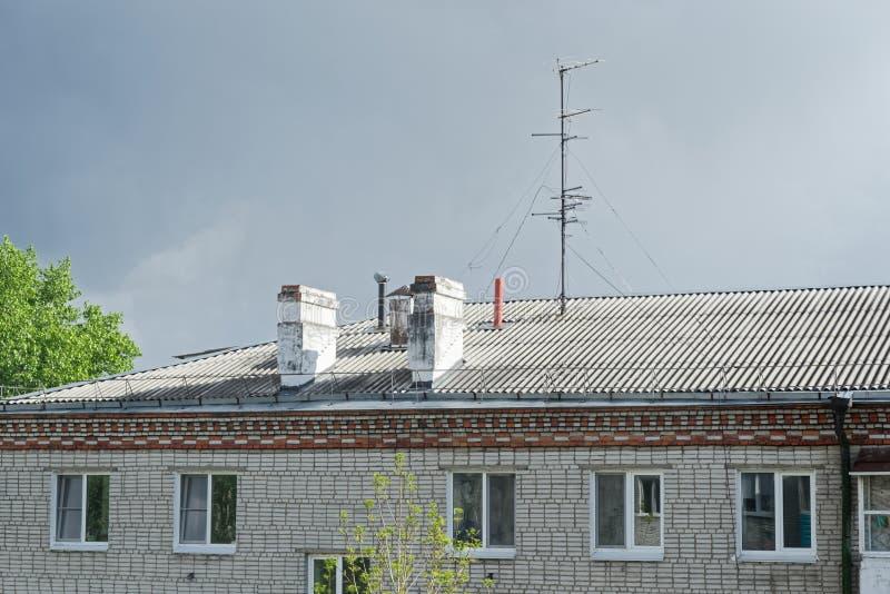 Chimeneas y antena de la televisión en el tejado del edificio de apartamentos contra el cielo nublado fotos de archivo