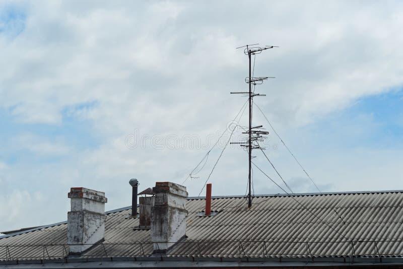 Chimeneas y antena en el tejado de un edificio de apartamentos contra el cielo nublado azul fotos de archivo
