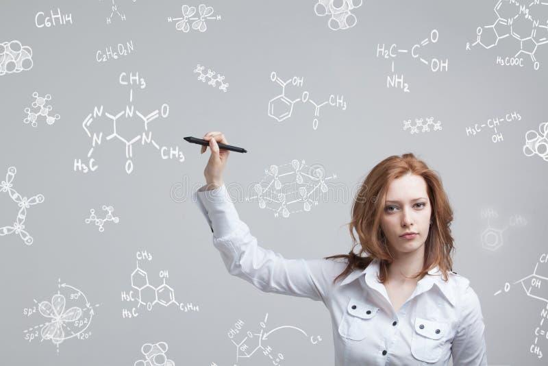 Chimico della donna che lavora con le formule chimiche su fondo grigio immagine stock libera da diritti