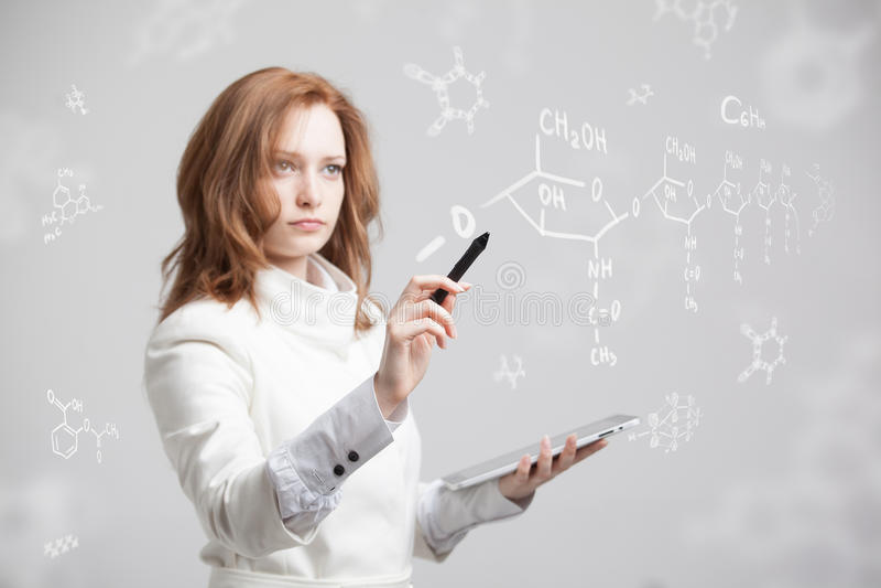 Chimico della donna che lavora con le formule chimiche su fondo grigio fotografia stock libera da diritti