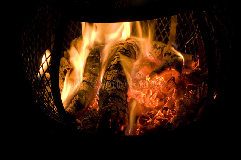 Chiminea Fire. A red hot fire burning in a backyard chiminea with red glowing embers stock images