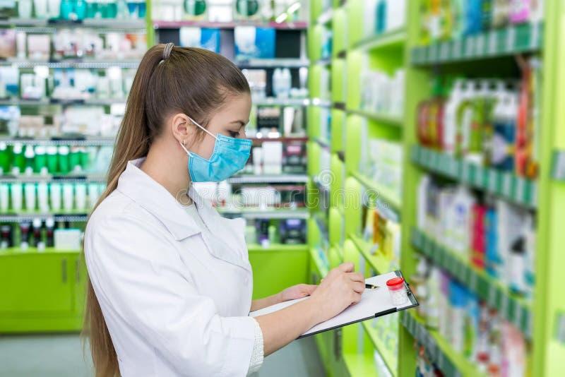 Chimiste de femme vérifiant la liste de médicament dans la pharmacie photos libres de droits
