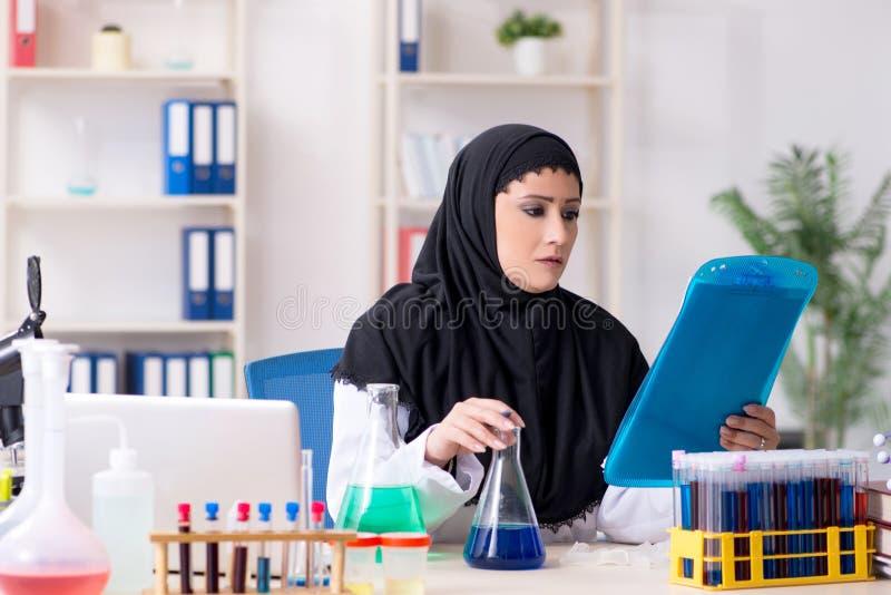 Chimiste f?minin dans le hijab fonctionnant dans le laboratoire photographie stock libre de droits