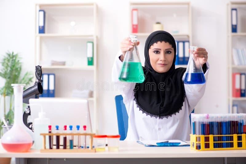 Chimiste f?minin dans le hijab fonctionnant dans le laboratoire images libres de droits