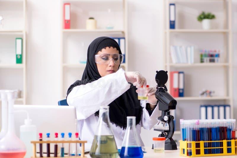 Chimiste f?minin dans le hijab fonctionnant dans le laboratoire photo libre de droits