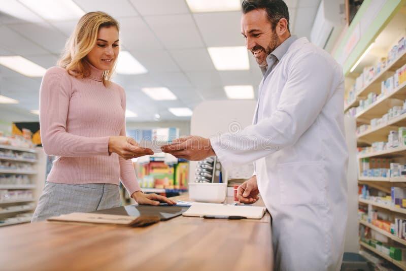 Chimiste prenant la prescription du client à la pharmacie photographie stock