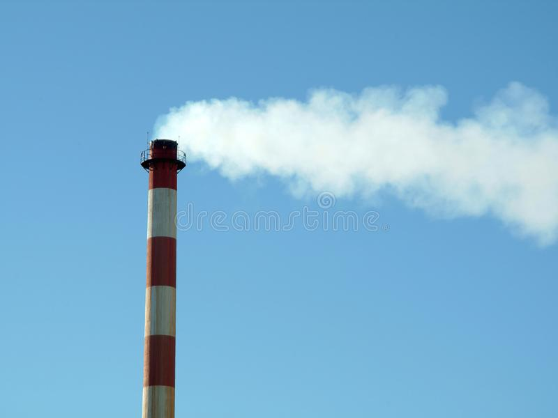 Chimney in factory expelling smoke royalty free stock photo