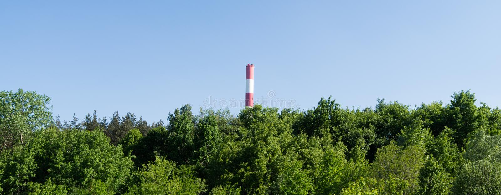 Chimney, power plant in green forest. Factory is located in ZÄ…bki, Poland, near Warsaw royalty free stock images