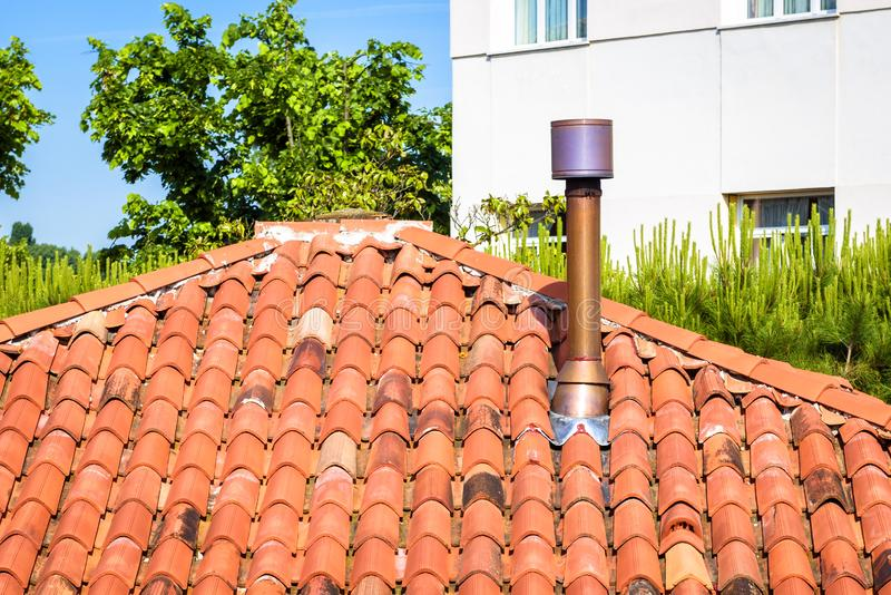 Chimney on roof of residential house. Home round chimney close-up in summer stock image