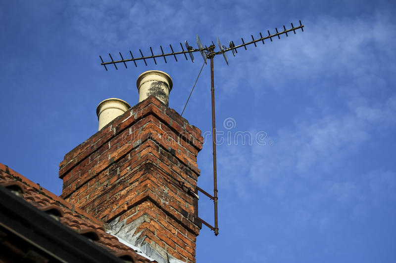 Chimney on a roof with TV aerial and blue sky with light cloud royalty free stock photos