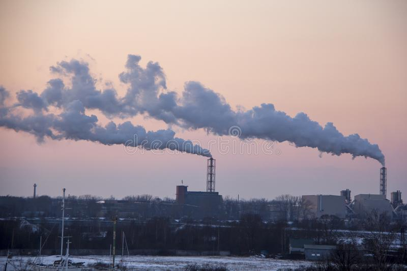 Chimney smoking stack on sunrise. Air pollution and climate change theme. stock photo