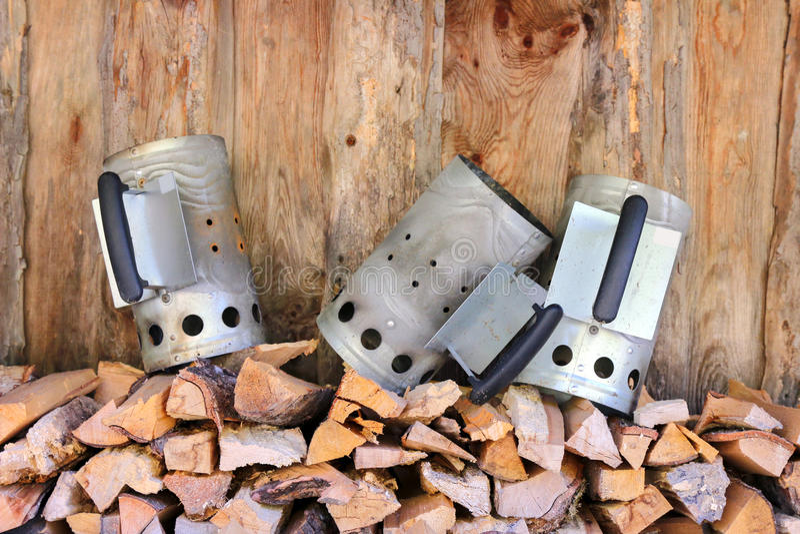 Chimney starters (Charcoal chimney). 3 Chimney starters (Charcoal chimney) on a stack of fire wood royalty free stock photography