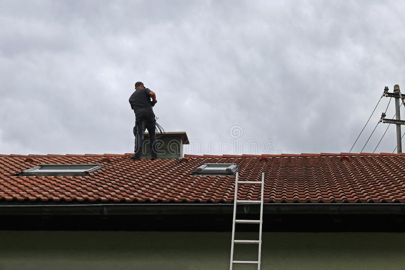 A chimney sweeper on the roof cleans a chimney with a brush royalty free stock images
