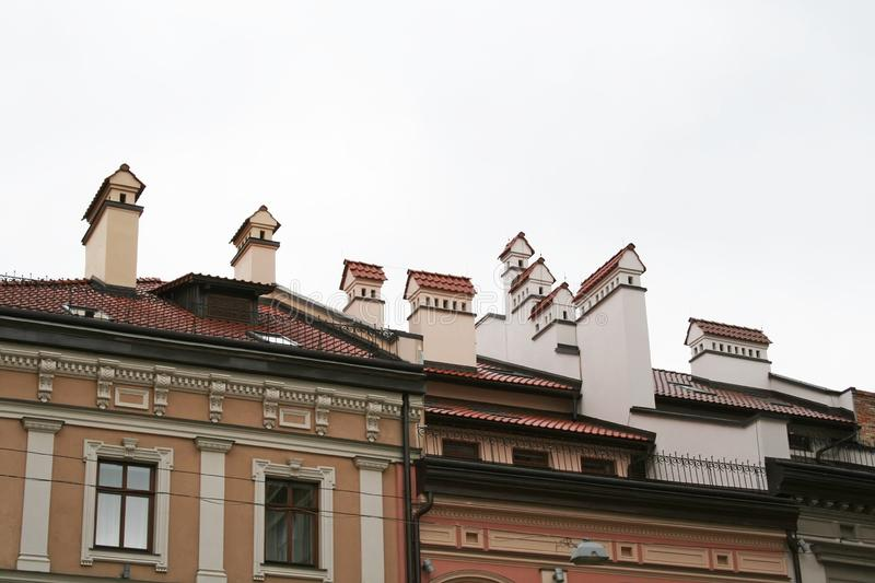 Chimneys in the form of small houses, located on the tiled roof of the house.  stock images