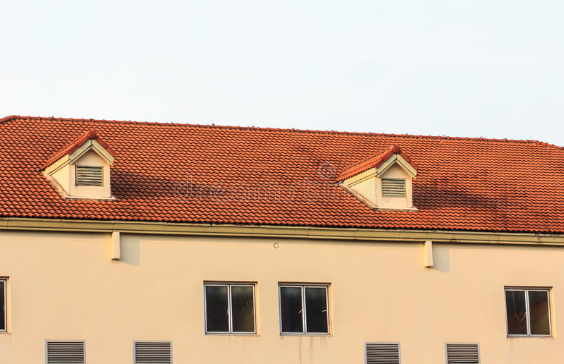 Chimneys on roof of red tiles with blue sky and clouds stock photo