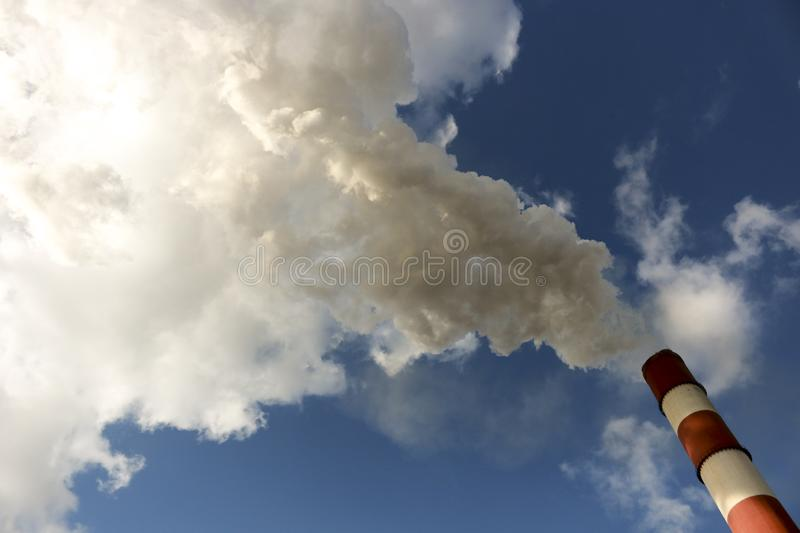 Chimneys with steam production of a thermal power station. Cloudy sky is polluted by smoke from the chimney stock image