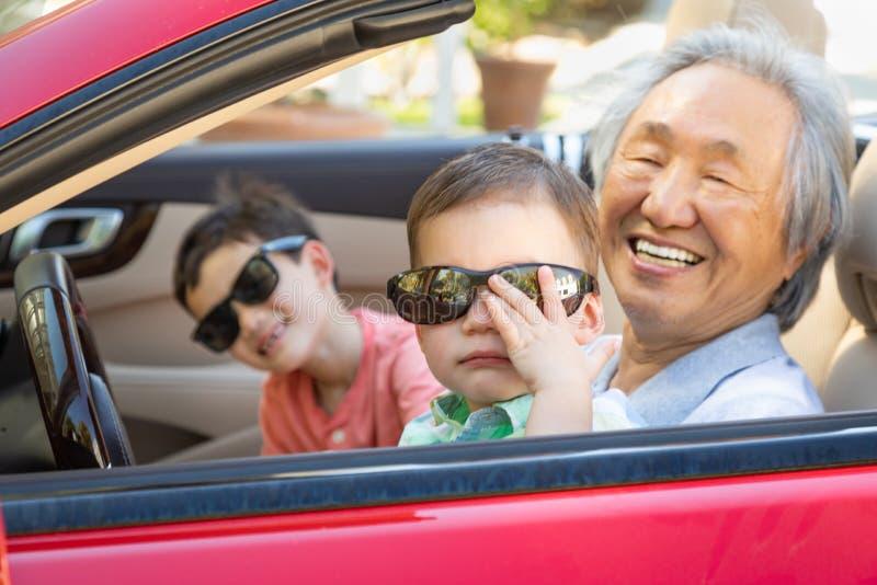 Chinês Granfather e crianças da raça misturada que jogam no carro estacionado imagem de stock