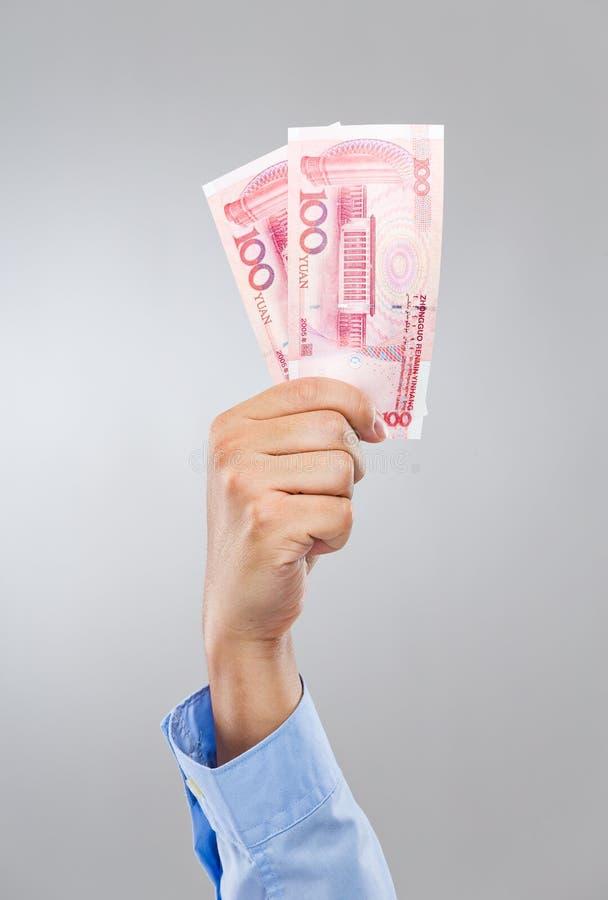 Chinês renminbi da posse cem da mão do homem de negócios imagens de stock royalty free