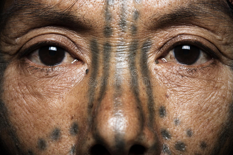 Chin tribe tattooed woman close up. MINDAT, MYANMAR - DECEMBER 7: Chin tribe tattooed woman (Muun) poses for a photo on December 7, 2015 Mindat, Myanmar. Chin stock images