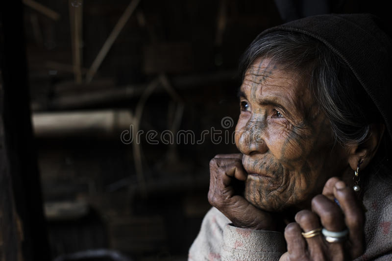 Chin tribe tattooed woman (Muun). MINDAT, MYANMAR - DECEMBER 8: Chin tribe tattooed woman (Muun) poses for a photo on December 8, 2015 Mindat, Myanmar. Chin stock image