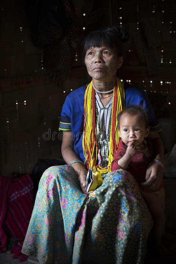 Chin tribe tattooed woman (Muun) and son. MINDAT, MYANMAR - DECEMBER 8: Chin tribe tattoed woman (Muun) poses for a photo with her son on December 8, 2015 Mindat royalty free stock photos