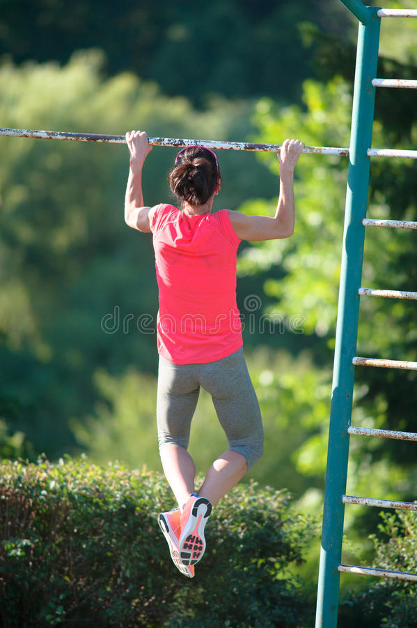 Chin-ups and Pullups training outdoors. Pull-up on the bar. Woman training stock image