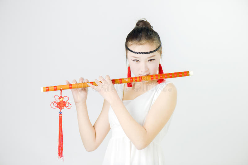 China beauty in blowing the flute royalty free stock photos
