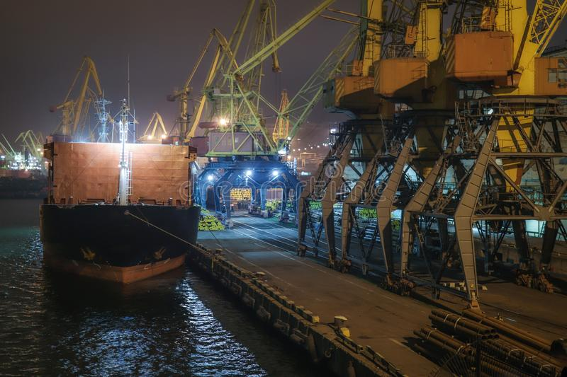 China. Cargo operation with bulk carrier vessel moored at pier. Big cargo terminal at seaport. royalty free stock photo