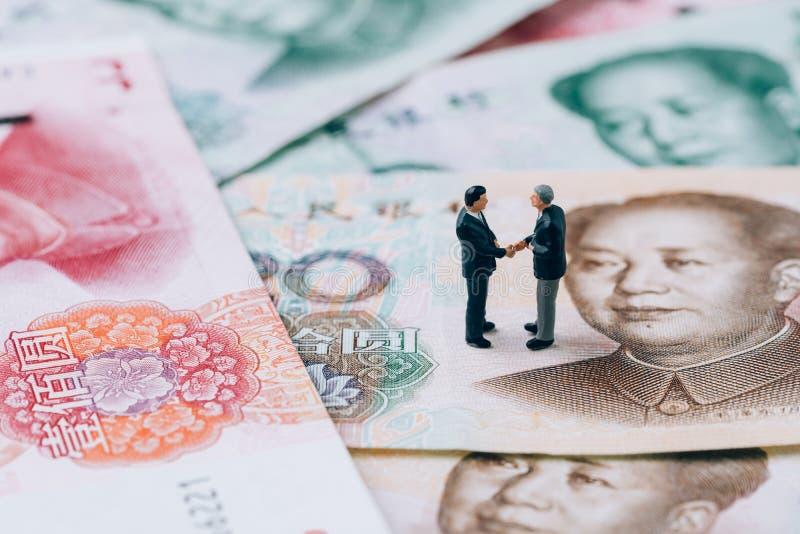 China finance tariff trade war negotiation talk concept, miniature people businessman leader handshaking on Chinese yuan banknote stock photo