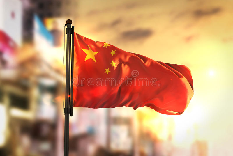 China Flag Against City Blurred Background At Sunrise Backlight. Sky royalty free stock photos