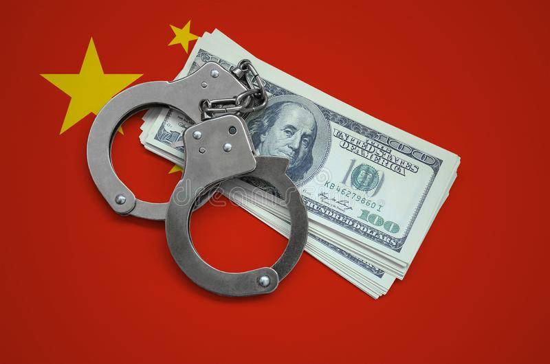 China flag with handcuffs and a bundle of dollars. Currency corruption in the country. Financial crimes royalty free stock photography