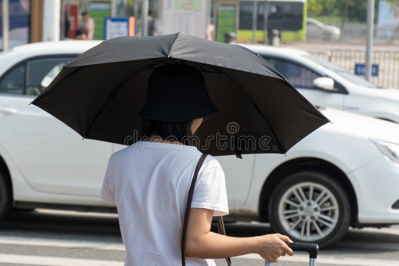 China, Guangzhou - October 19, 2019: Guangzhou City Railway Station. A Chinese girl with a black umbrella goes on the road to catc. H a taxi. White car stock images