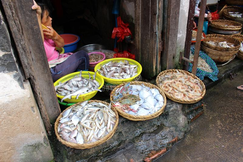 Saleswoman of fresh fish in the Asian market royalty free stock photography