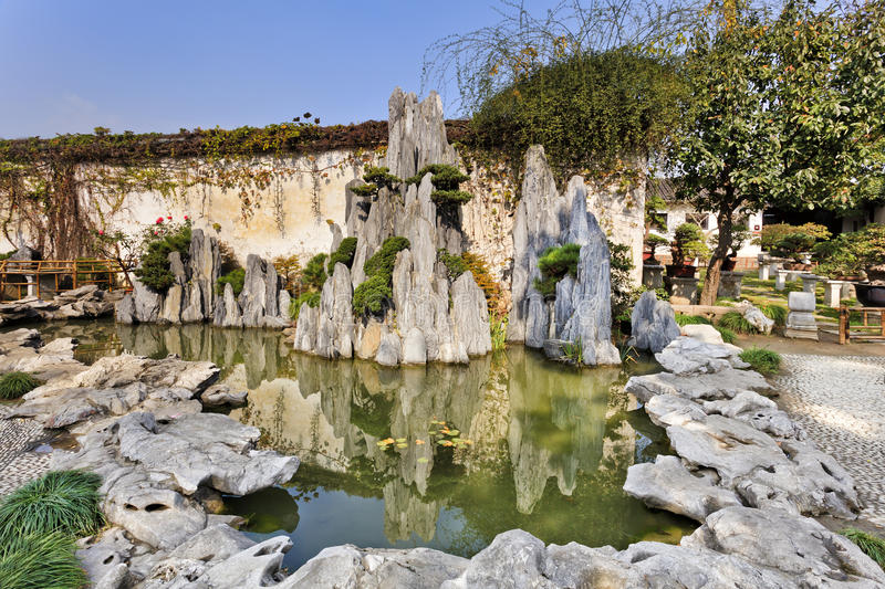 China Nanjing Garden Rocks pond. Miniature rocky pond with still reflective water in botanic chinese garden of small rocks and made-up landscape in Nanjing royalty free stock photo