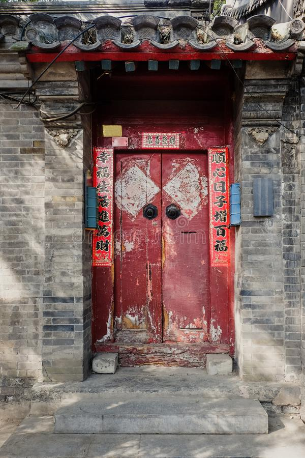 China Red Door with Mandarin writing in old hutong in Beijing, China. Writing on door mean good wishes as Lunar New Year royalty free stock images