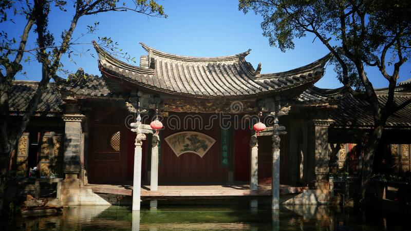 China& x27;s distinctive and beautiful ancient architectural art. ,The ancient stage next to the pond contrasts with the trees on either side stock image