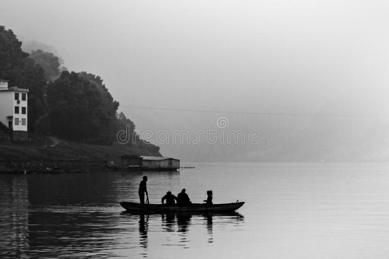 On a cloudy day, a small boat is floating on the Xin`An river of China. stock photos
