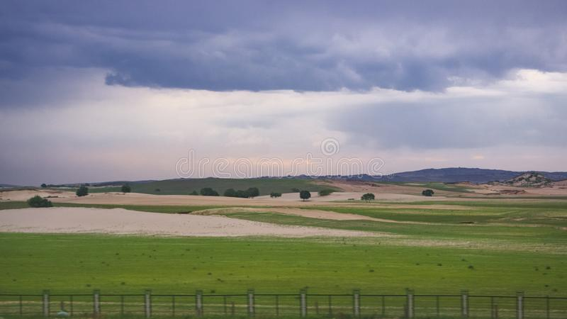 The scenery of the K1518 train passing by. China, the scenery of the K1518 train passing by, there are grasslands, deserts, desertification areas, and sunset royalty free stock photos