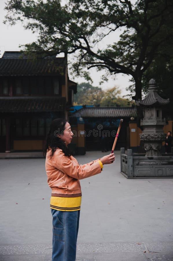 CHINA, SHANGHAI - 7 DE NOVEMBRO DE 2017: A mulher chinesa está rezando em um templo budista e em umas varas ardentes do incenso imagens de stock royalty free