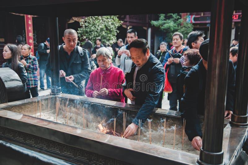 CHINA, SHANGHAI - 7 DE NOVEMBRO DE 2017: Os povos asiáticos estão rezando em um templo budista e em umas varas ardentes do incens imagem de stock