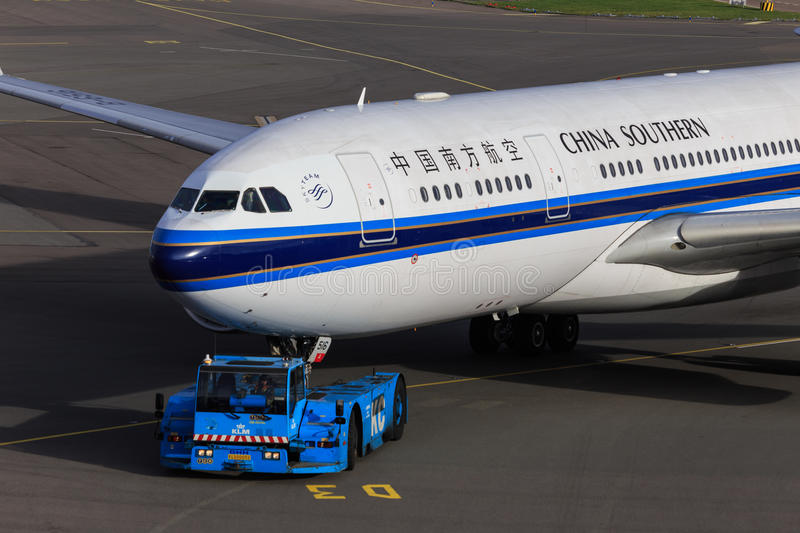 China Southern jet being towed. A China Southern Airlines Airbus A330 is being towed by a KLM tug royalty free stock photos