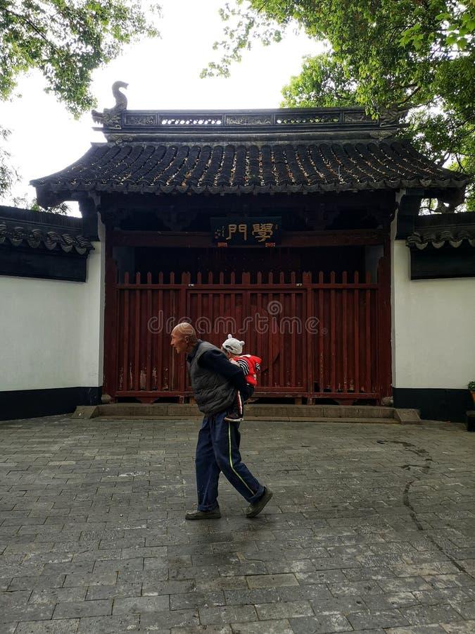 China Street scene, opa die een jong kind vervoert voor de oude Confucius tempel royalty-vrije stock foto's