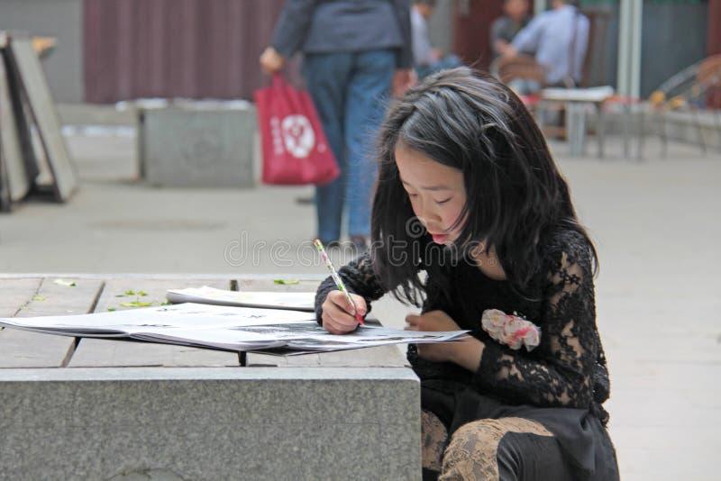 China, Suzhou - 14 de abril de 2012 Una muchacha china dibuja en un libro o pinta imágenes imágenes de archivo libres de regalías