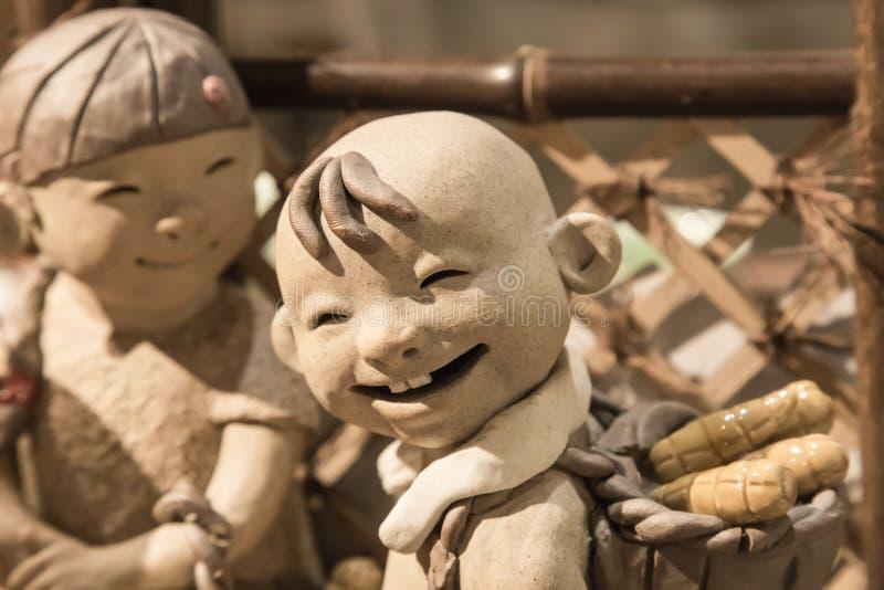 China, Suzhou 18 DE AGOSTO DE 2017: figura opinión del muchacho de los niños de la cerámica de la cara de la sonrisa del primer fotos de archivo