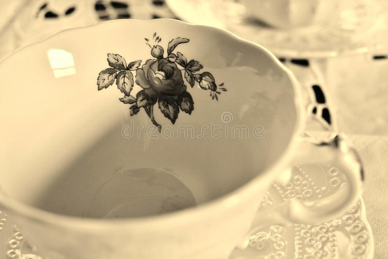 China Tea Cup in Sepia Tones. A china tea cup on a saucer with a lace tablecloth in sepia tones evokes a Victorian mood, a memory of grandparents, and perhaps stock images